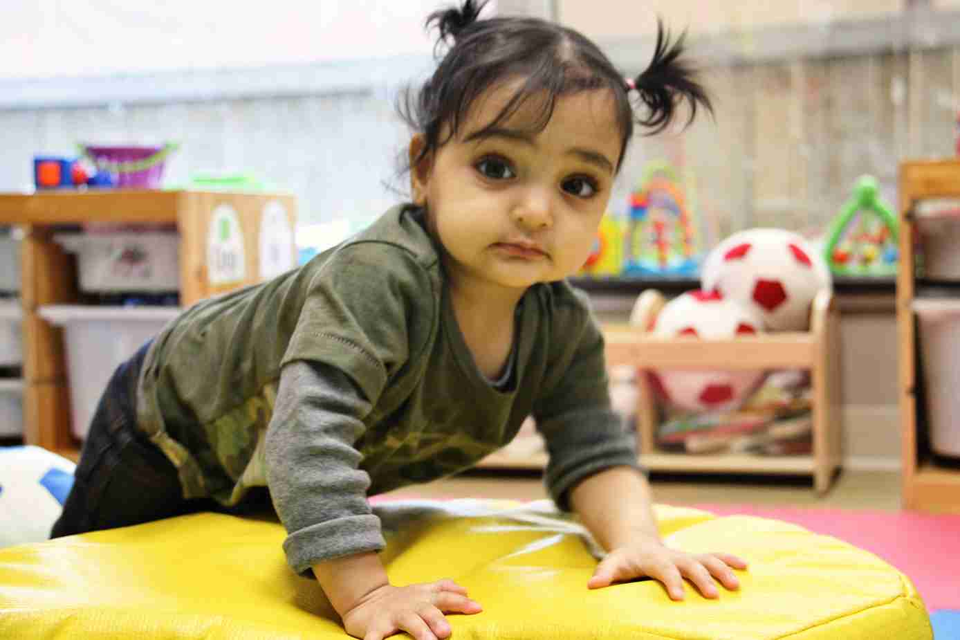 Baby leaning forward on a yellow mat