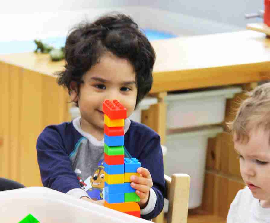Child playing and building a tower using lego