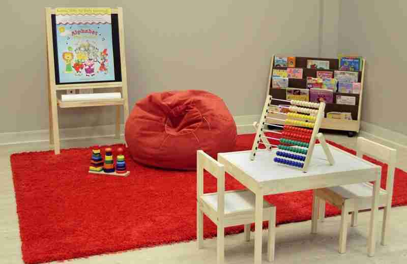 Delta room with Montessori educational toys, books, red playmat, and red beanie chair