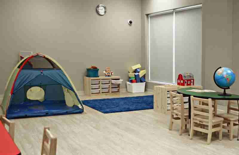 A tent, playmat, educational toys, and table with globe in the Gamma room