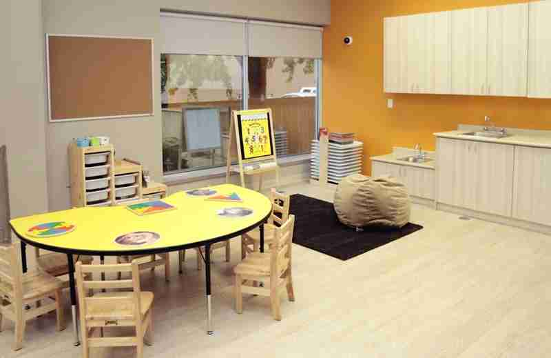 Interior of room for 5 and 6-year olds with table, sink, and play area.