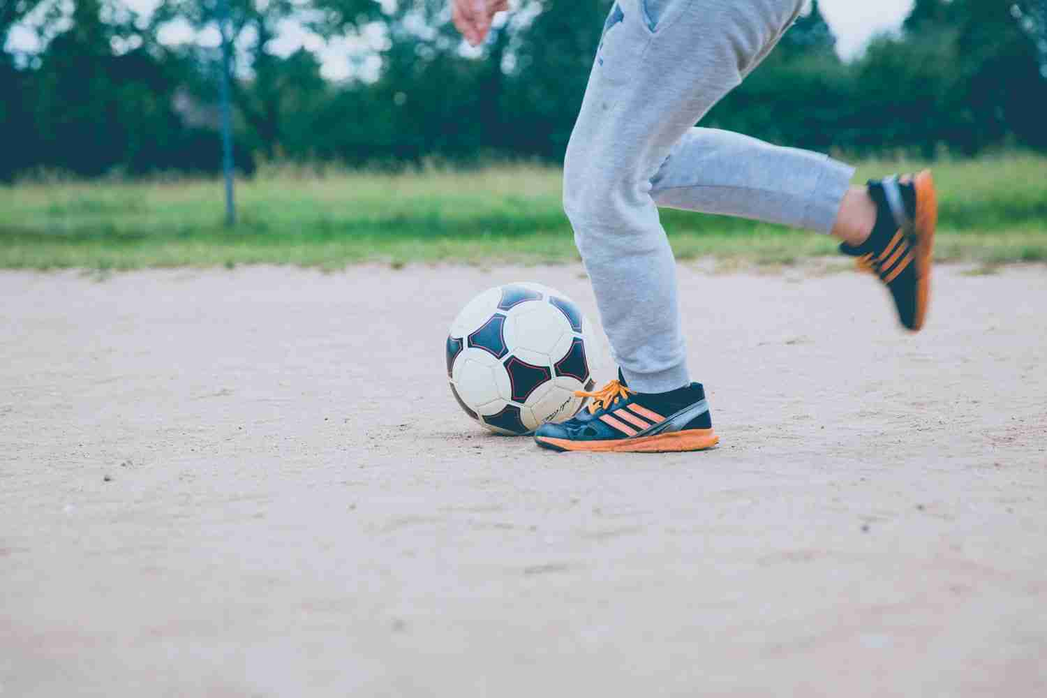 Kicking soccer ball to stay active as part of raising healthy kids
