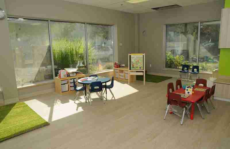 Interior of SimplySmart Child Care Centre with blue and red table and chairs, green mats, and educational toys