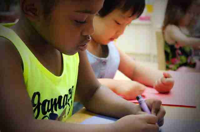 Children coloring with crayon