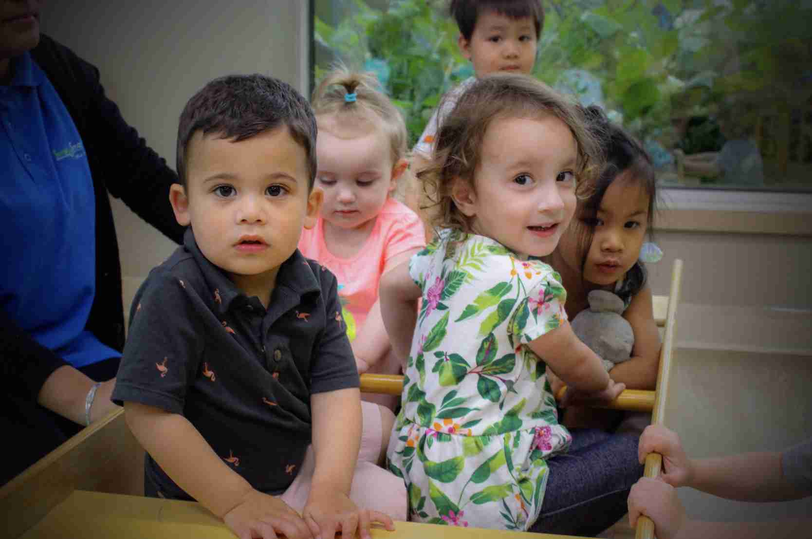 Little children playing on a cart
