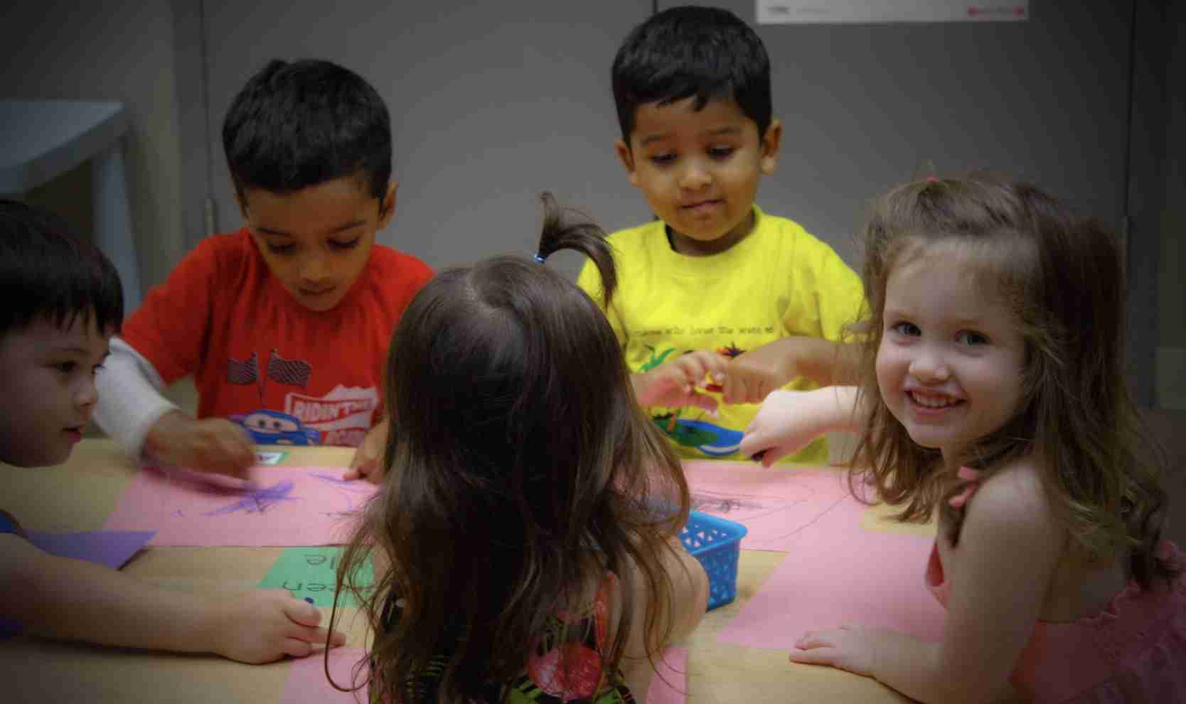 Children coloring pink paper sheets on a table