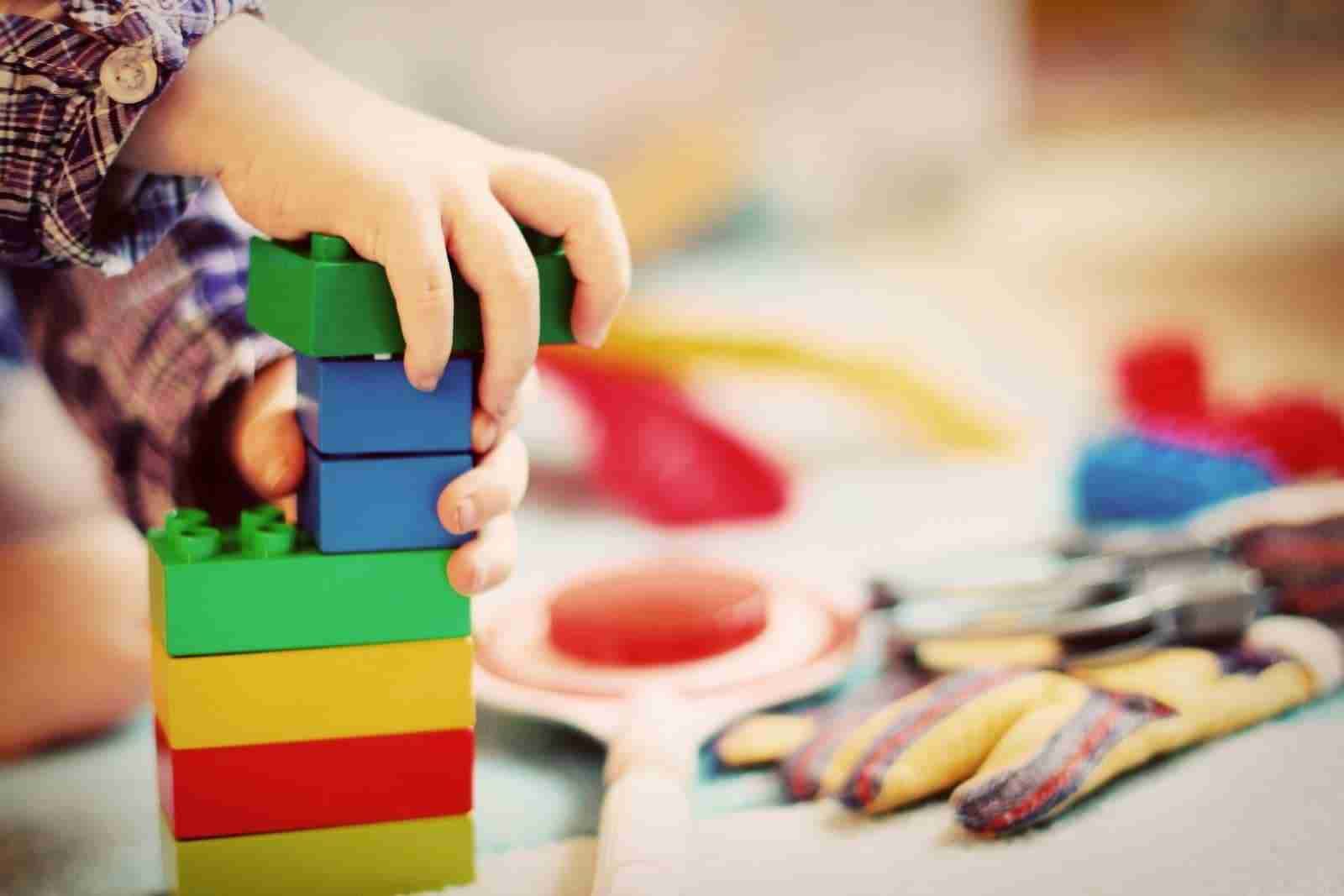Child in Kindergarten playing with lego blocks