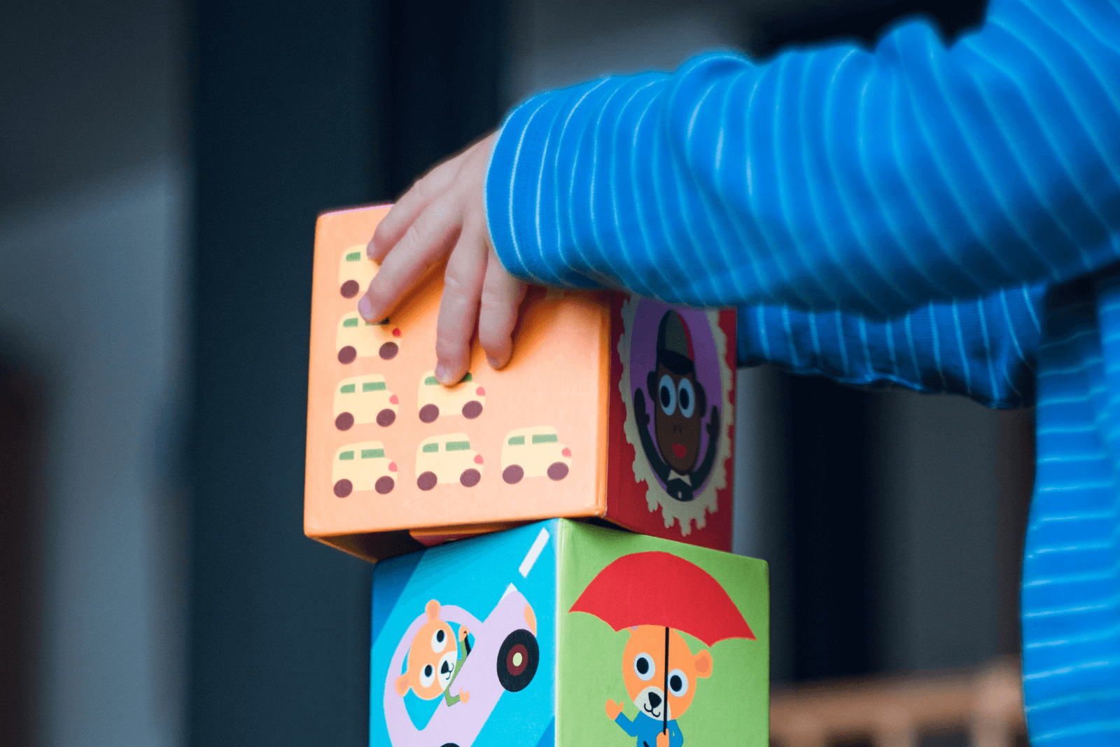 Child learning to play with wooden blocks