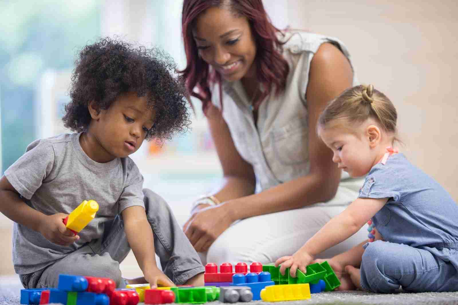 Children playing in daycare with their teacher