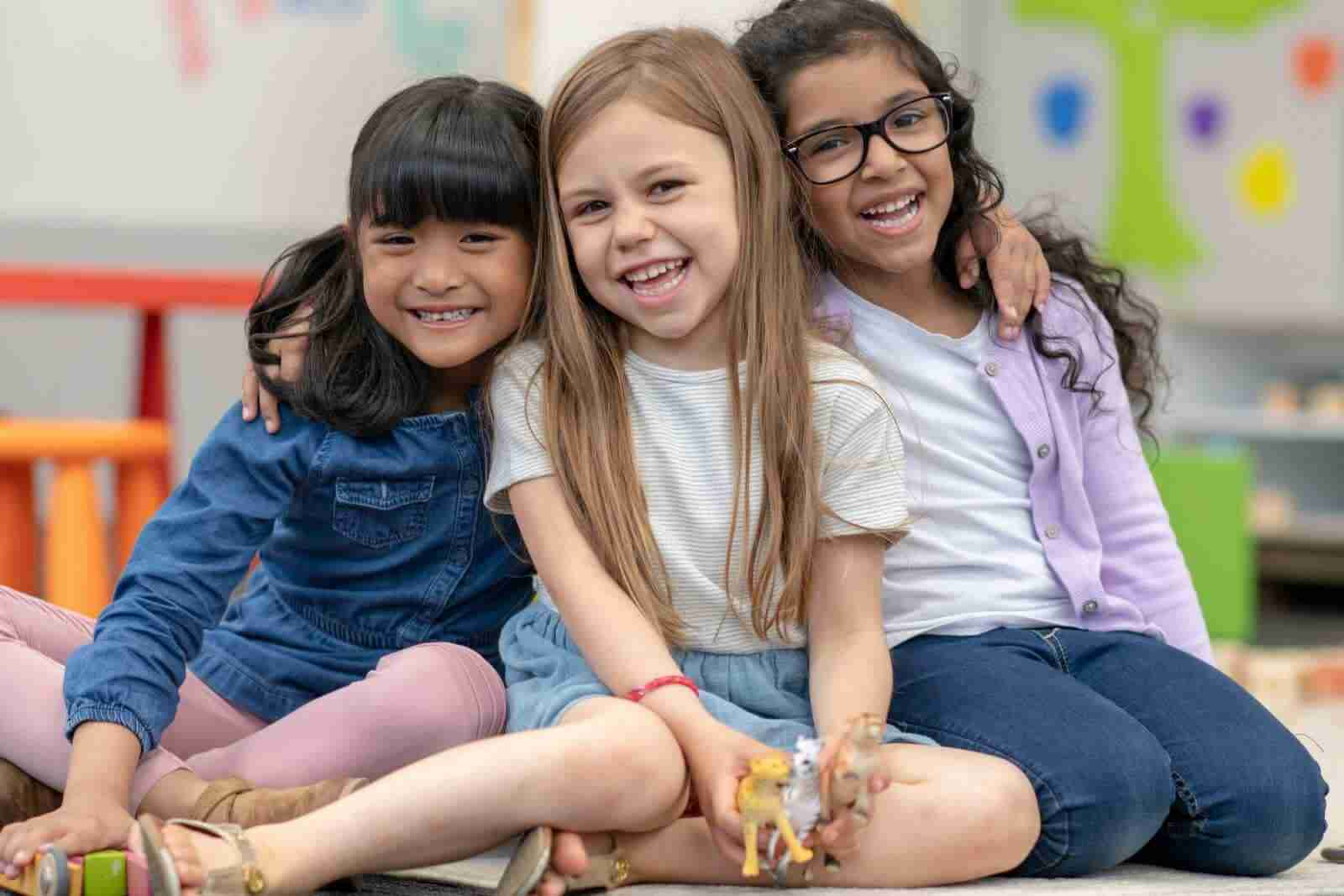 Three children expressing happy feelings. Teaching children about their feelings