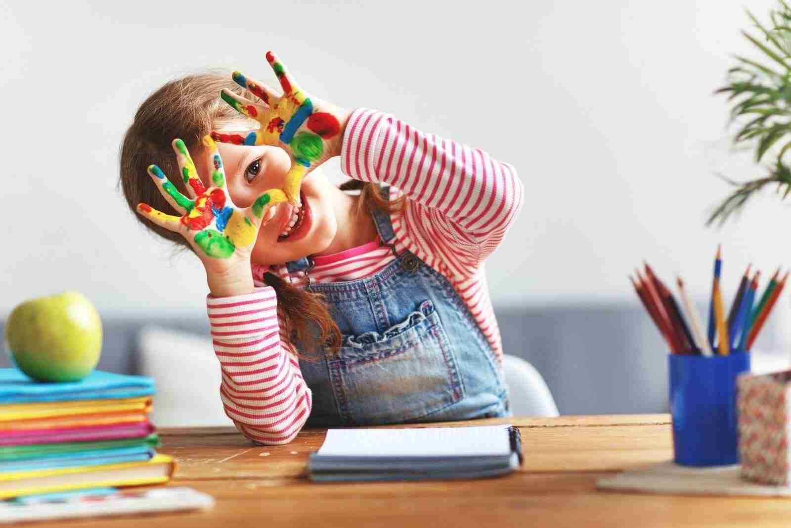 Young child with paints on her hands developing her five senses