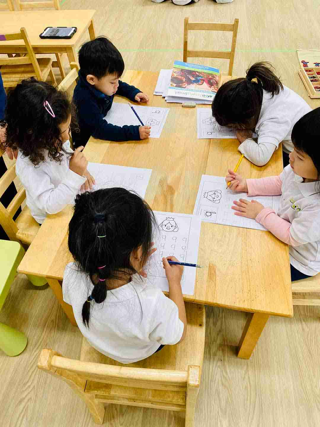 Five children sitting around a table and writing on their worksheet