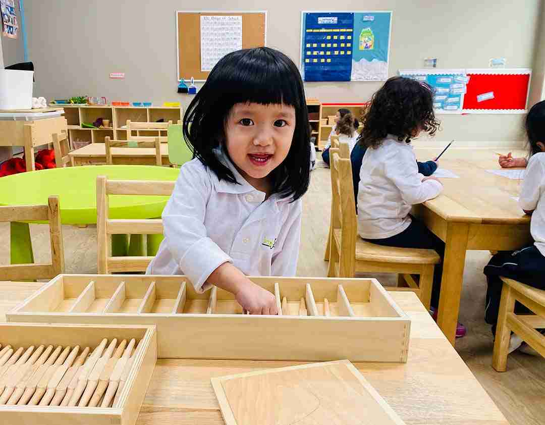 Child smiling while playing with educational toy at SimplySmart Childcare Centre