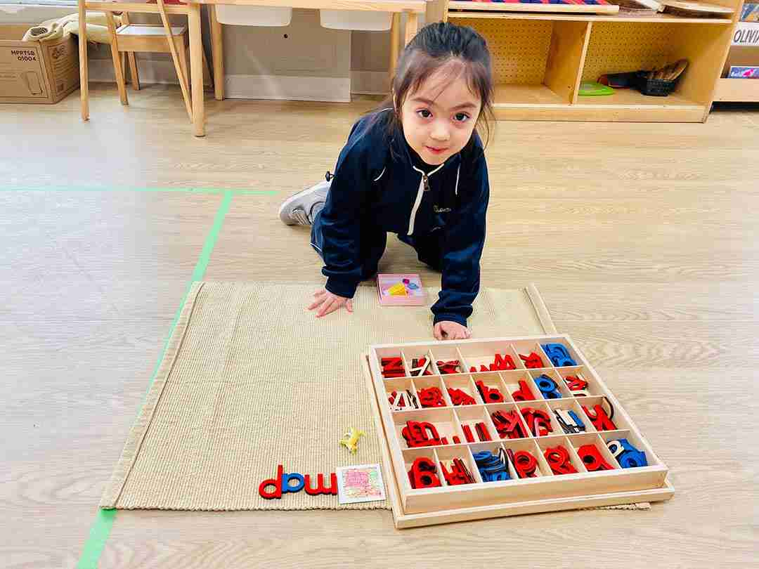 Child playing with wooden red and blue letters at SimplySmart Oakville at Sinclair Road